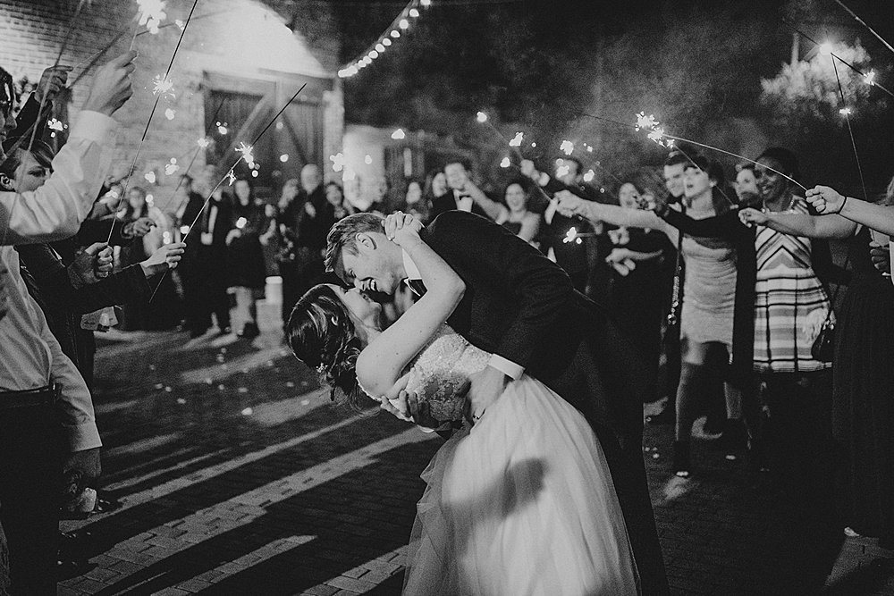 couple shares a kiss during their sparkler send off