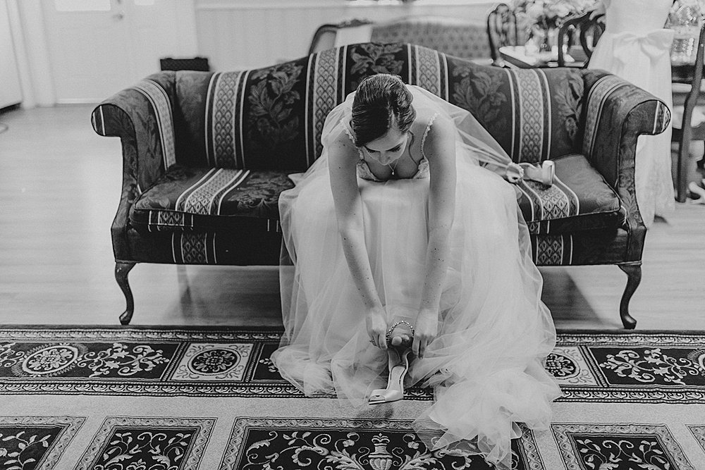 Bride putting the finishing touches on getting dressed for her fall wedding at the Silk Mill