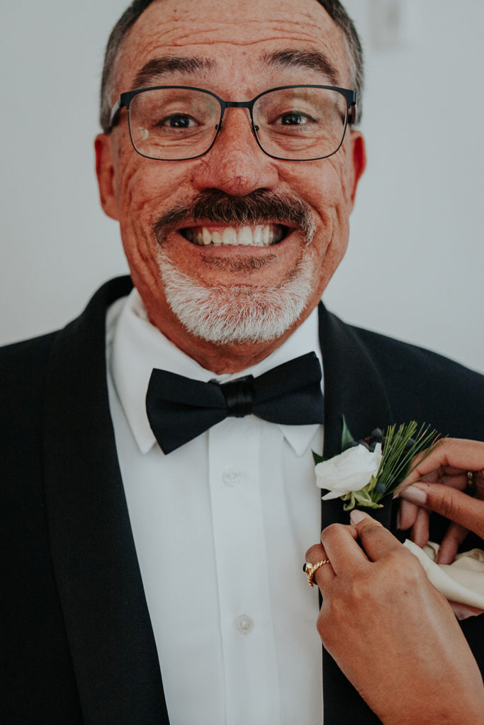 Father of the groom grins as his boutonniere is pinned before ceremony