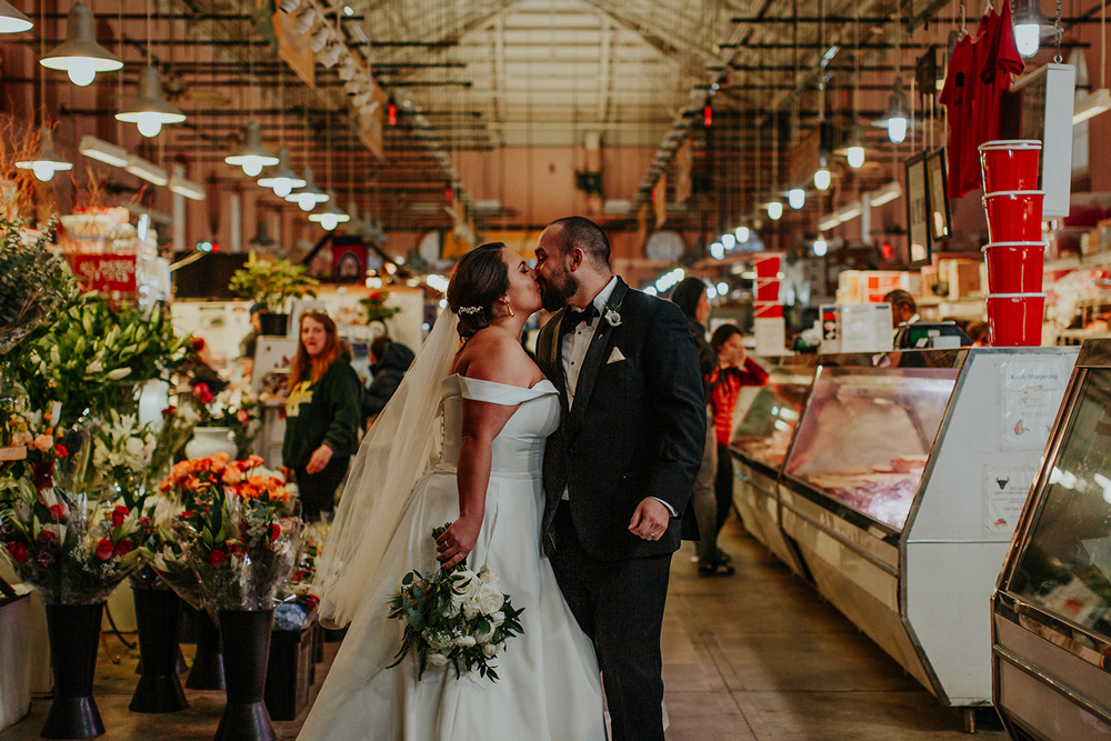 Couple shares a kiss before wedding reception at Eastern Market