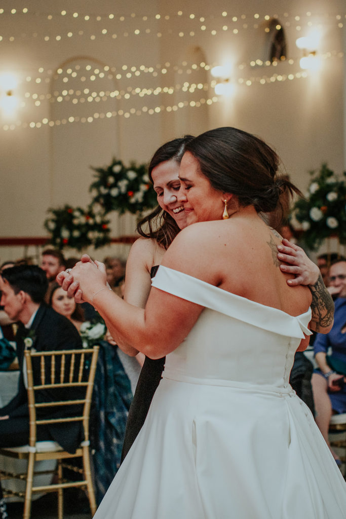 the bride and her sister share a special dance as they honor their father's memory