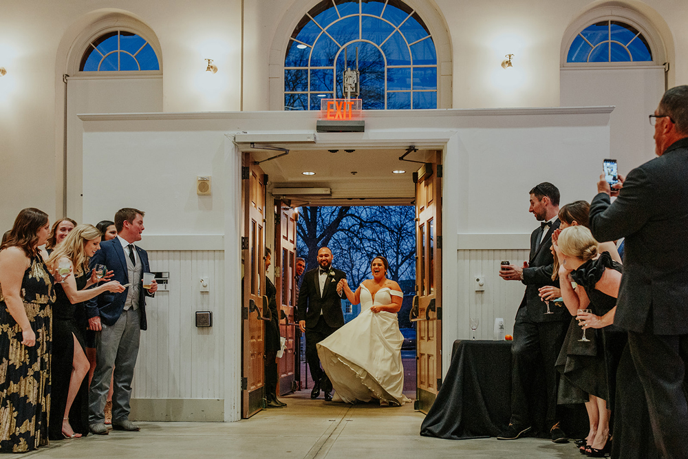 a couple joyfully enters their DC wedding reception, surrounded by family and friends