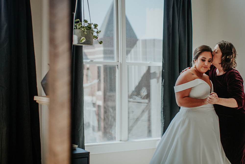 a bride and her mother sharing a special moment while getting ready