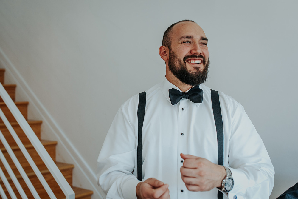 Groom smiles and laughs with groomsmen during getting ready
