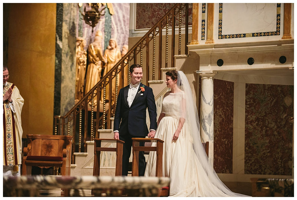 couple enjoying a moment during the wedding ceremony at St Matthew's Cathedral, DC