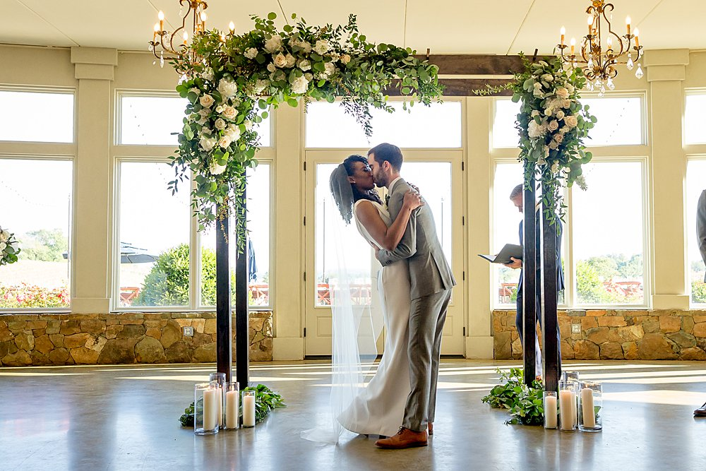 Couple exchanging a kiss at the end of their ceremony, with arch in background