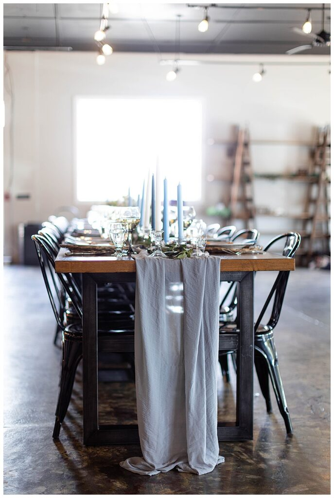 tablescape with taper candles and grey runner in industrial wedding venue