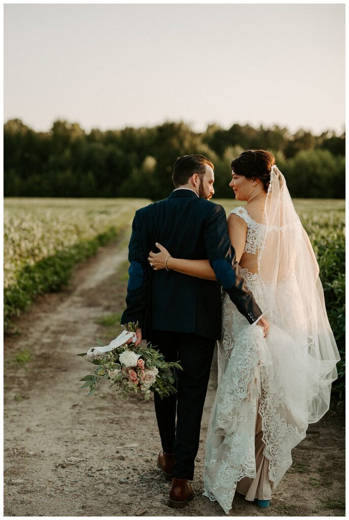 Groom holding his bride's train during golden hour photos