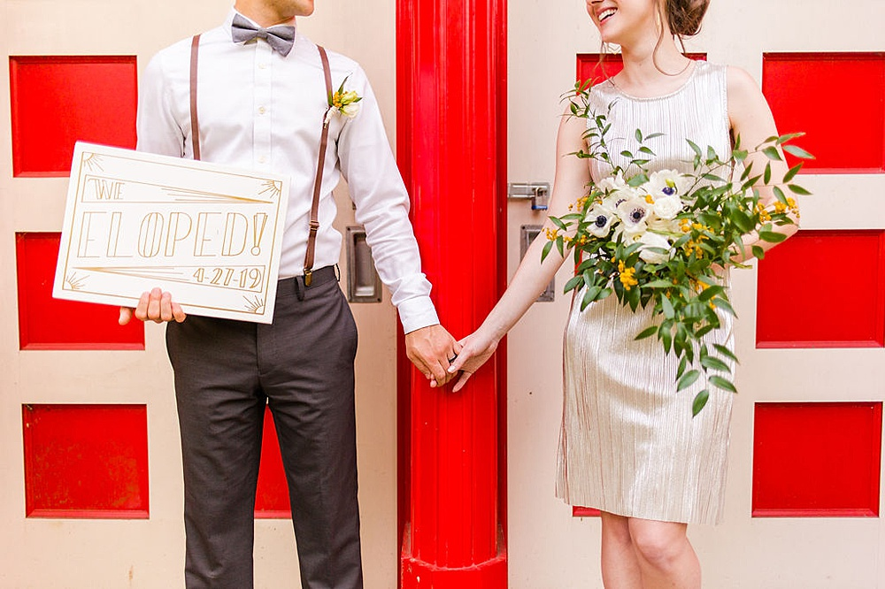 """Bride and groom are holding hands in front of a white and red entrance door, groom is holding a sign that read """"We eloped"""", bride is holding a flower bouquet."""