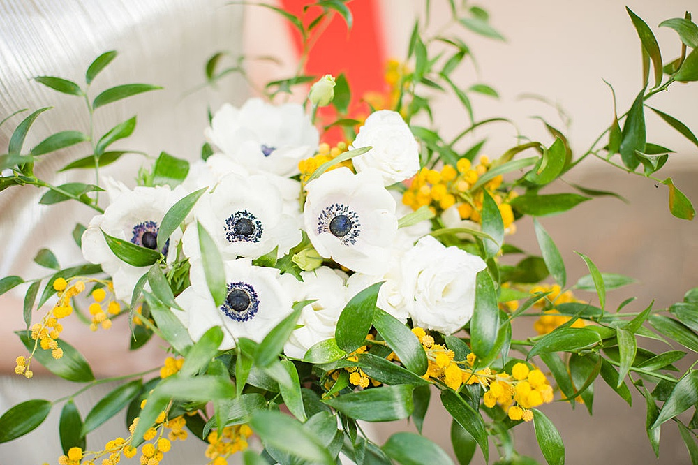 Picture of a flower bouquet of Italian ruscus, mimosa flowers and anemones.